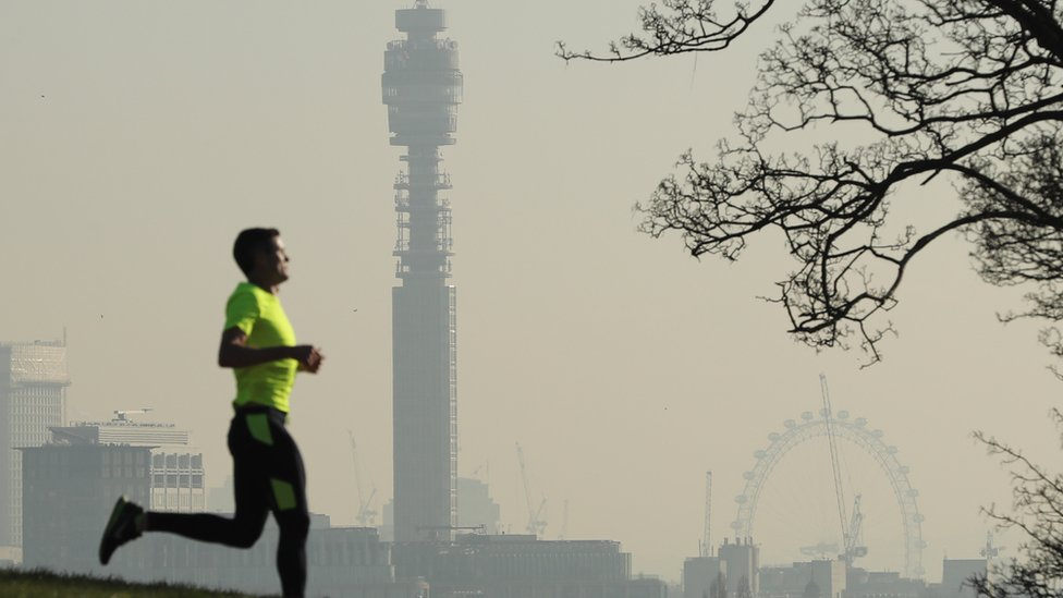 A man running against a backdrop of a London skyline showing polluted air