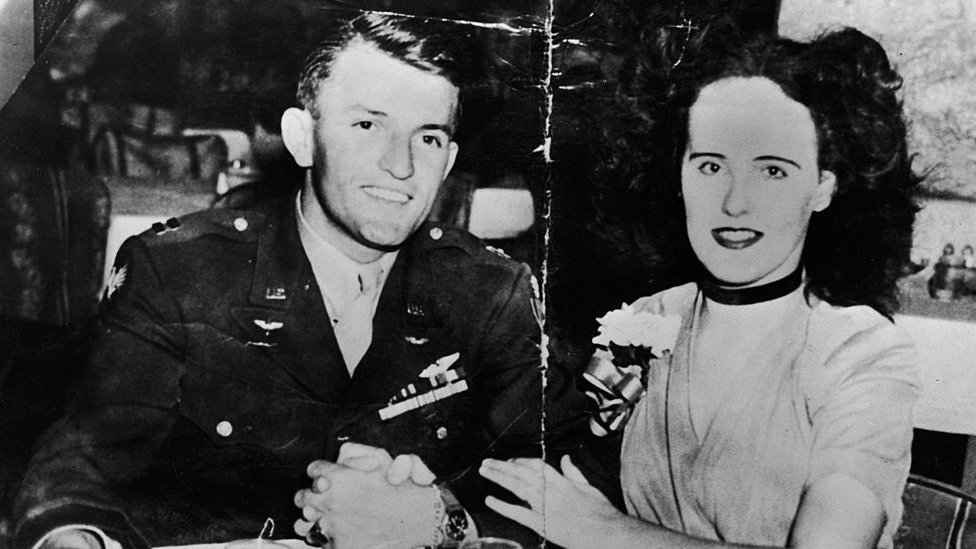 American aspiring actress and murder victim Elizabeth Short (1924 - 1947), known as the 'Black Dahlia,' sits arm-in-arm at a restaurant or bar table with American Army Major Matthew M. Gordon Jr (? - 1945), mid 1940s.