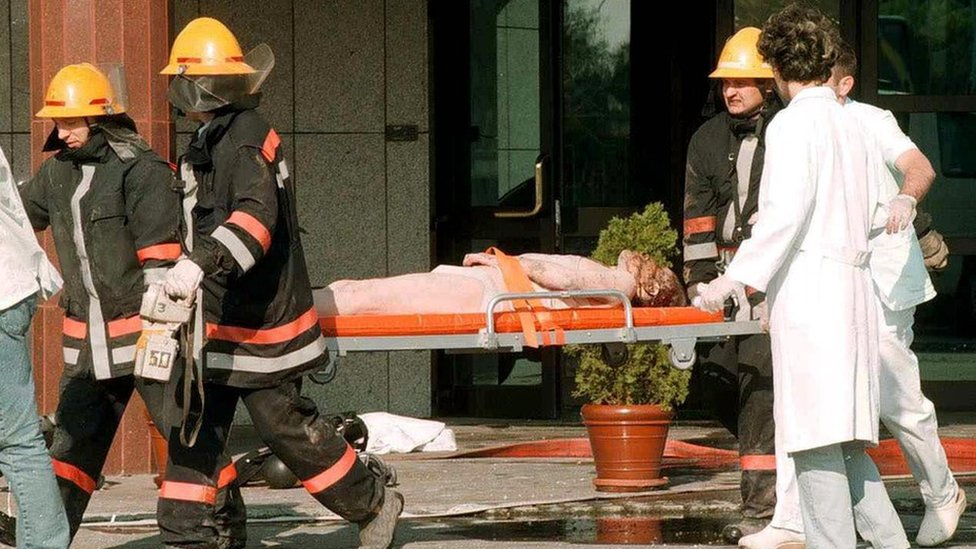 Unidentified injured Chinese embassy staff is carried away on a stretcher by Yugoslav rescue workers after the fire at the Chinese embassy, early Saturday, 08 May 1999,
