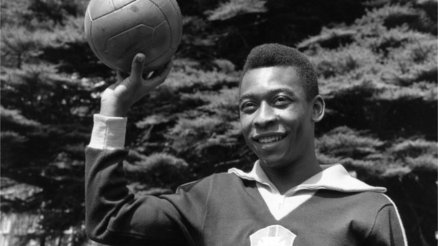 Pele as a young man holding a football above his head
