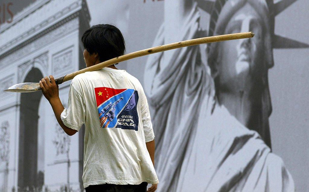 一名建築工作者走過北京一處豪華小區的廣告牌前,廣告牌背景是巴黎凱旋門與紐約的自由女神像。