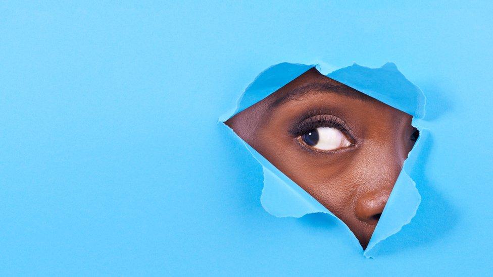 Mujer mirando por un agujero.