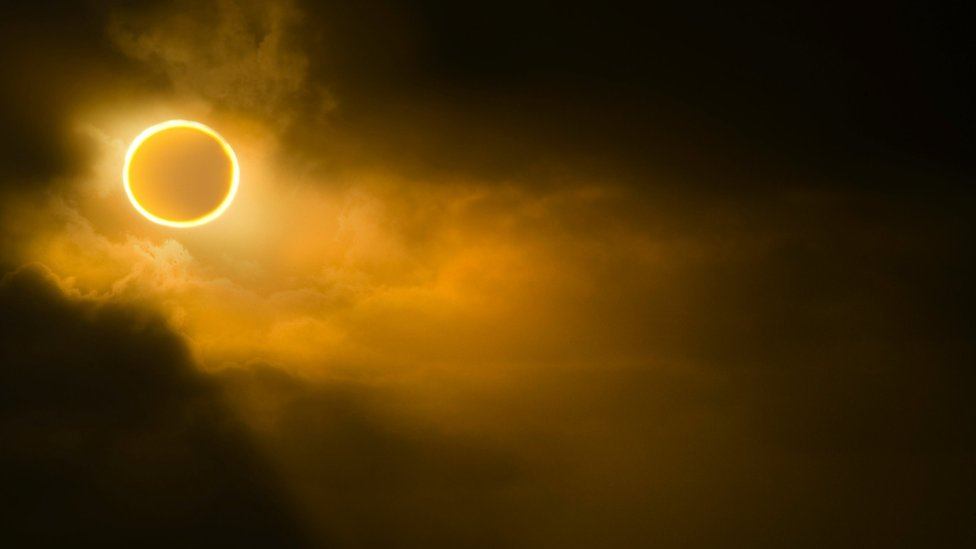 Low angle view of solar eclipse in sky during foggy weather.