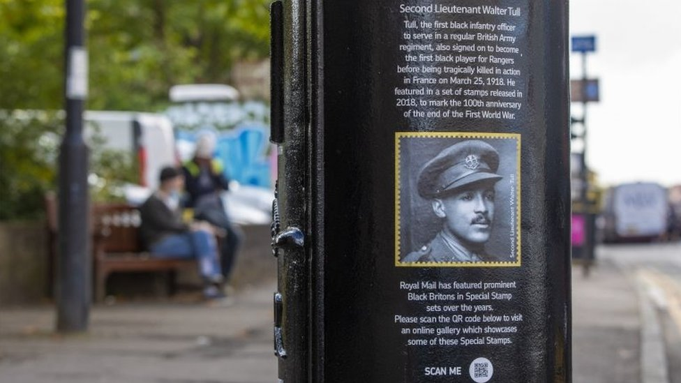 A black postbox featuring an image of Second Lieutenant Walter Tull in Byres Road, Glasgow