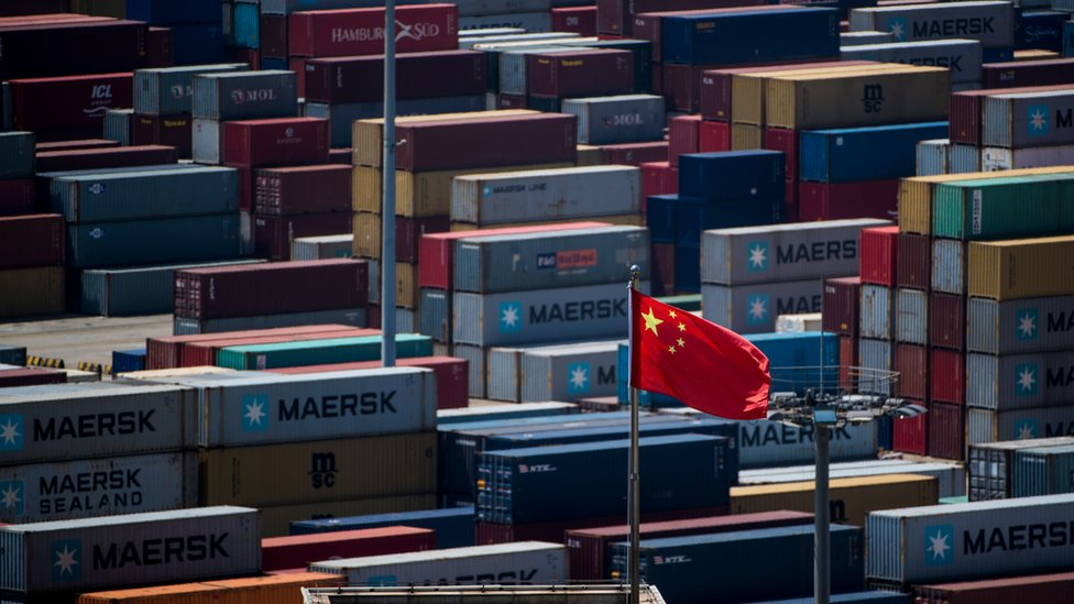 A Chinese flag is seen in front of containers at the Yangshan Deep-Water Port,