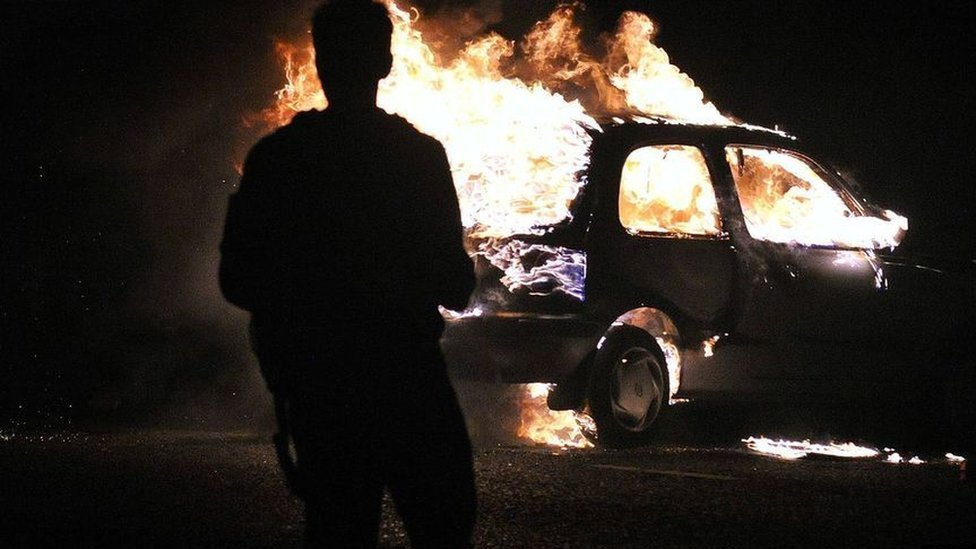 Coche ardiendo durante unos disturbios.