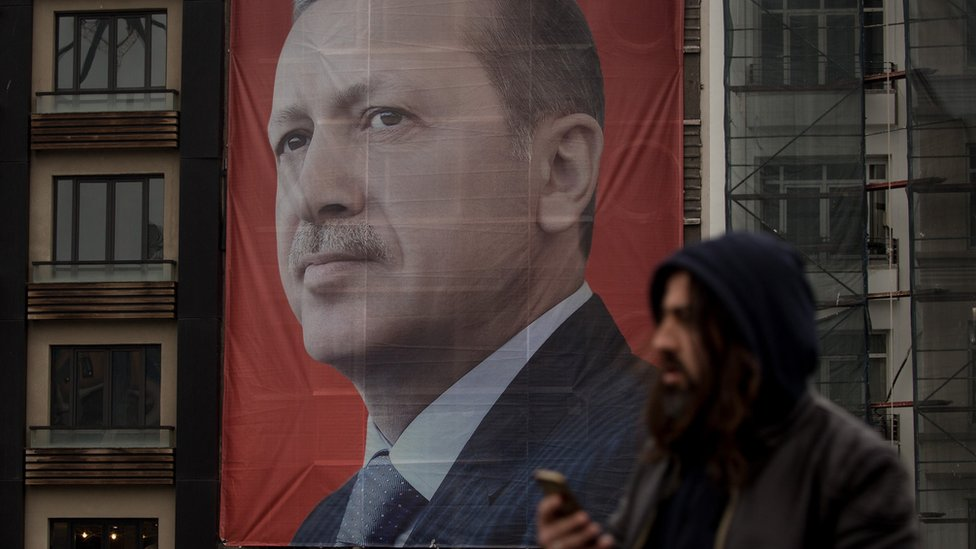People walk past a large banner showing a portrait of Turkish President Recep Tayyip Erdogan in Taksim Square, Istanbul, 13 March