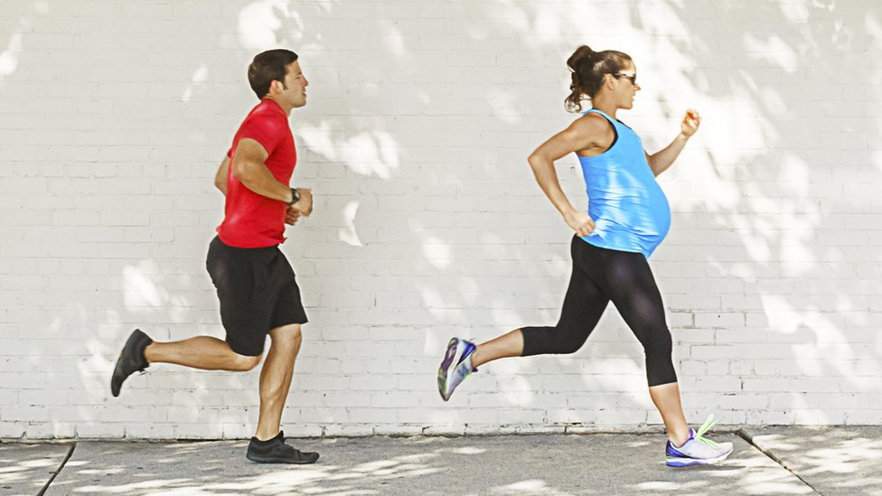 A man and a pregnant woman training