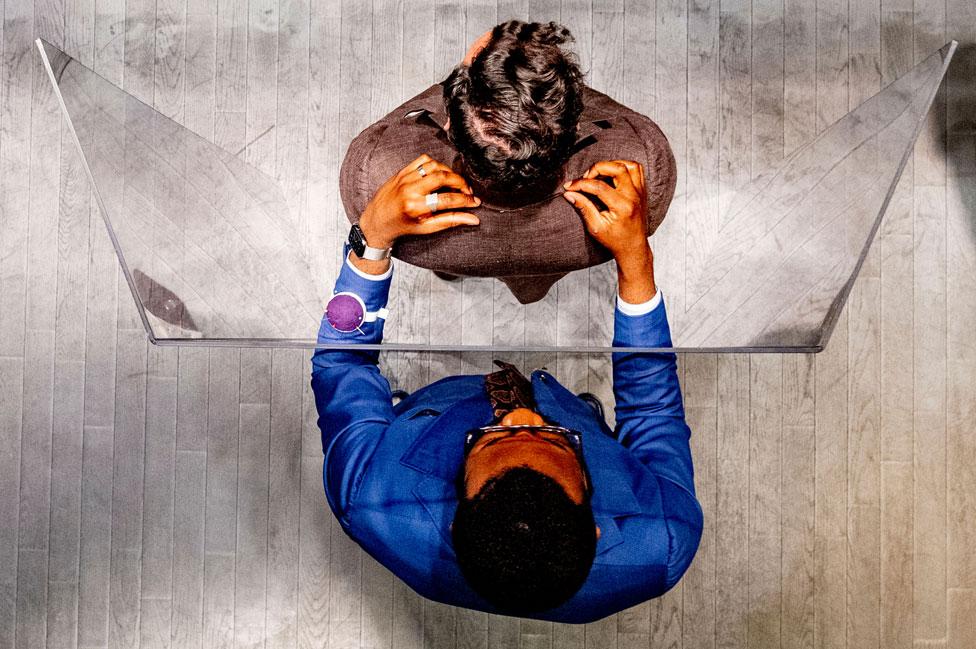 Un sastre en Países Bajos trabaja con un cliente, separado por una gran barrera de acrílico con espacios para meter sus brazos.