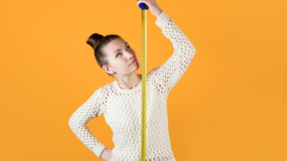 Una mujer mide su estatura