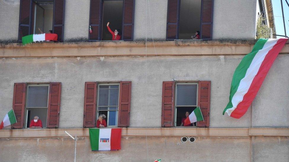 Gente recluida en sus casas en Italia, durante el confinamiento
