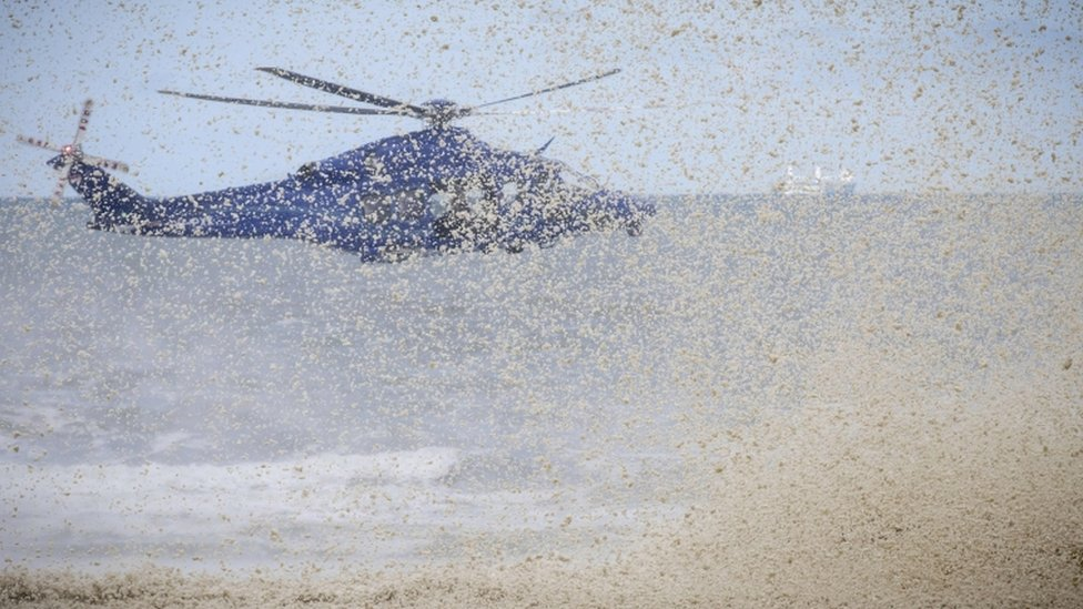 The downdraft from a police helicopter blows away surf from beachside rocks in Scheveningen, The Netherlands, on May 14, 2020