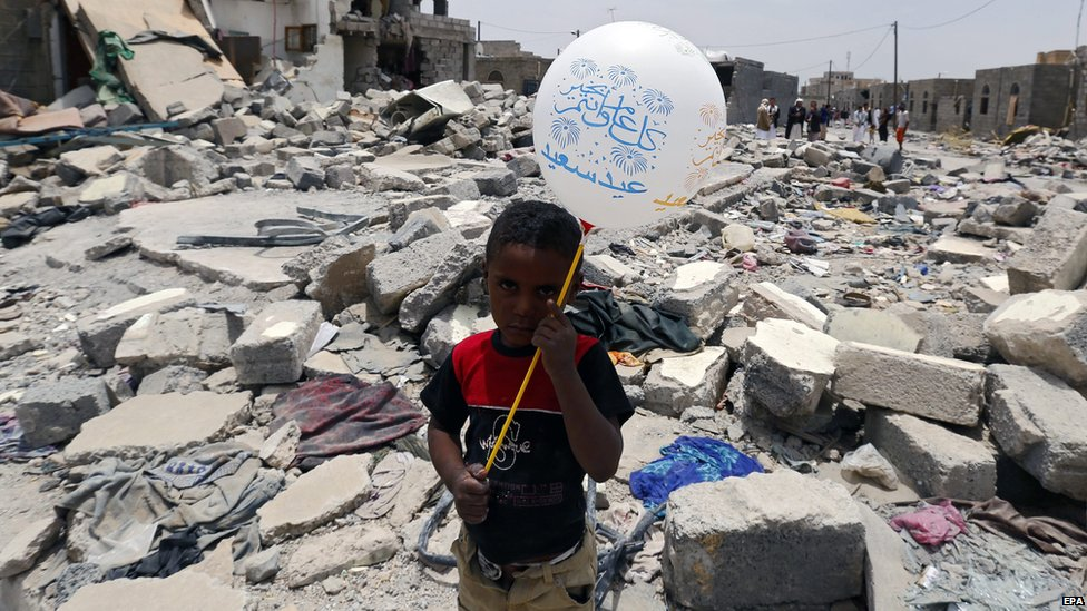 A Yemeni boy holds a balloon next to destroyed houses during the Muslim festival of Eid on 18 July, 2015