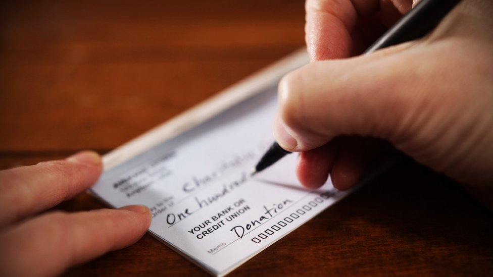 A person writes a donation cheque in this close-up photo