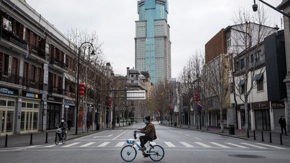 A man cycles along an empty street on February 8, 2020 in Wuhan, Hubei province, China.
