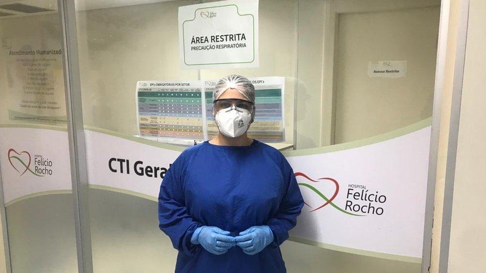 Psicóloga com equipamentos de proteção posa em hospital