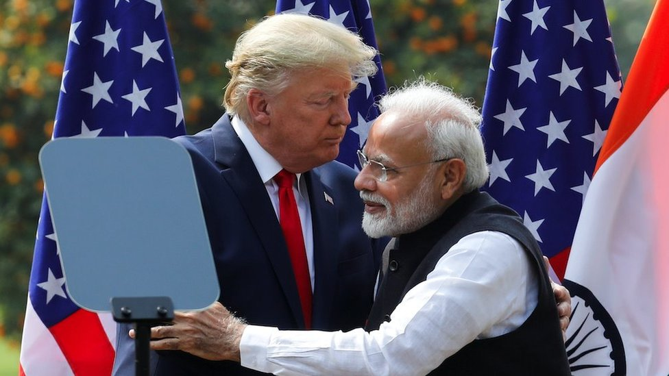 """US President Donald Trump and India""""s Prime Minister Narendra Modi embrace during a joint news conference after bilateral talks at Hyderabad House in New Delhi, India, February 25, 2020."""
