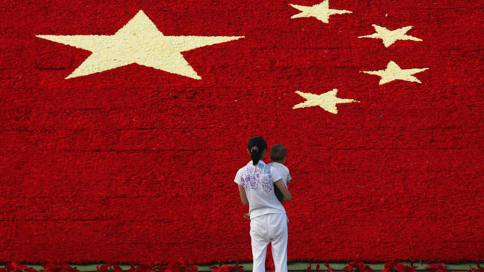 A woman holds her son as she looks at the national flag made up of 100,000 carnations at Wuling Square September 25, 2007 in Hangzhou, China