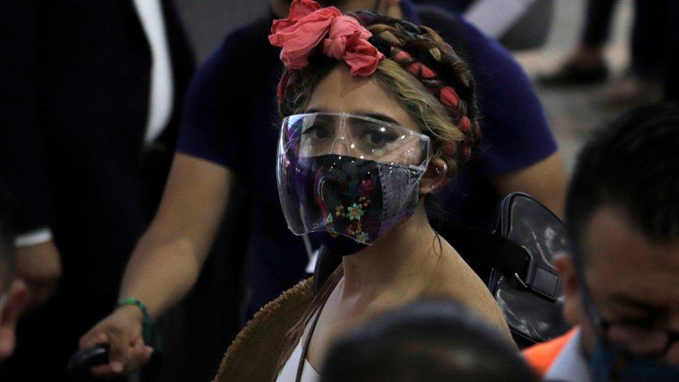 Mulher de face shield e máscara
