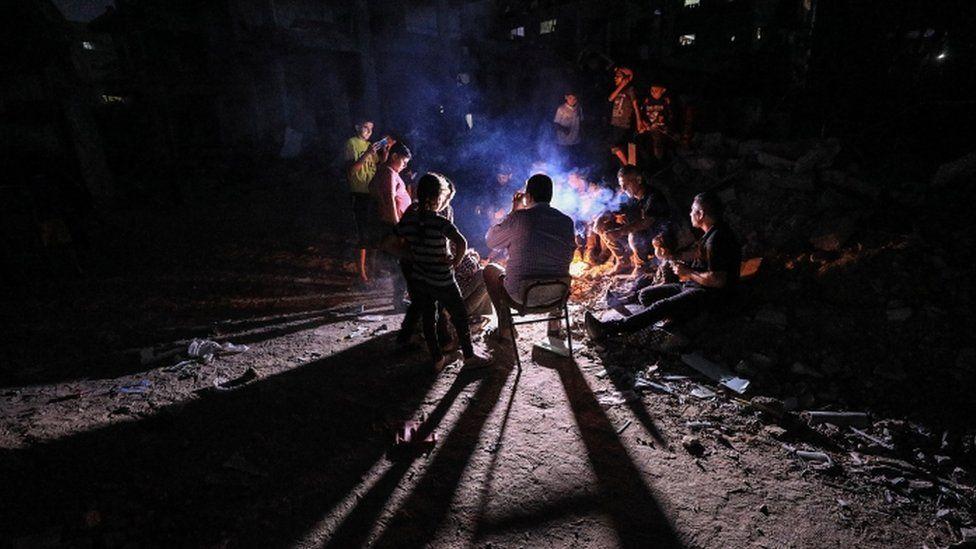 أشخاص يجلسون على حطام منزل مدمر في غزة