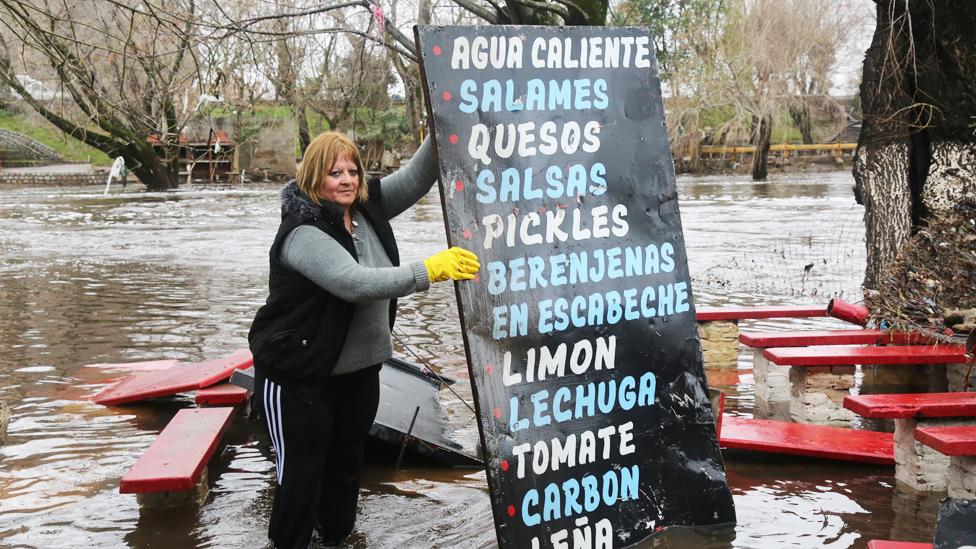 Mujer en Argentina sostiene un cartel con una lista de verduras en una una calle inundada
