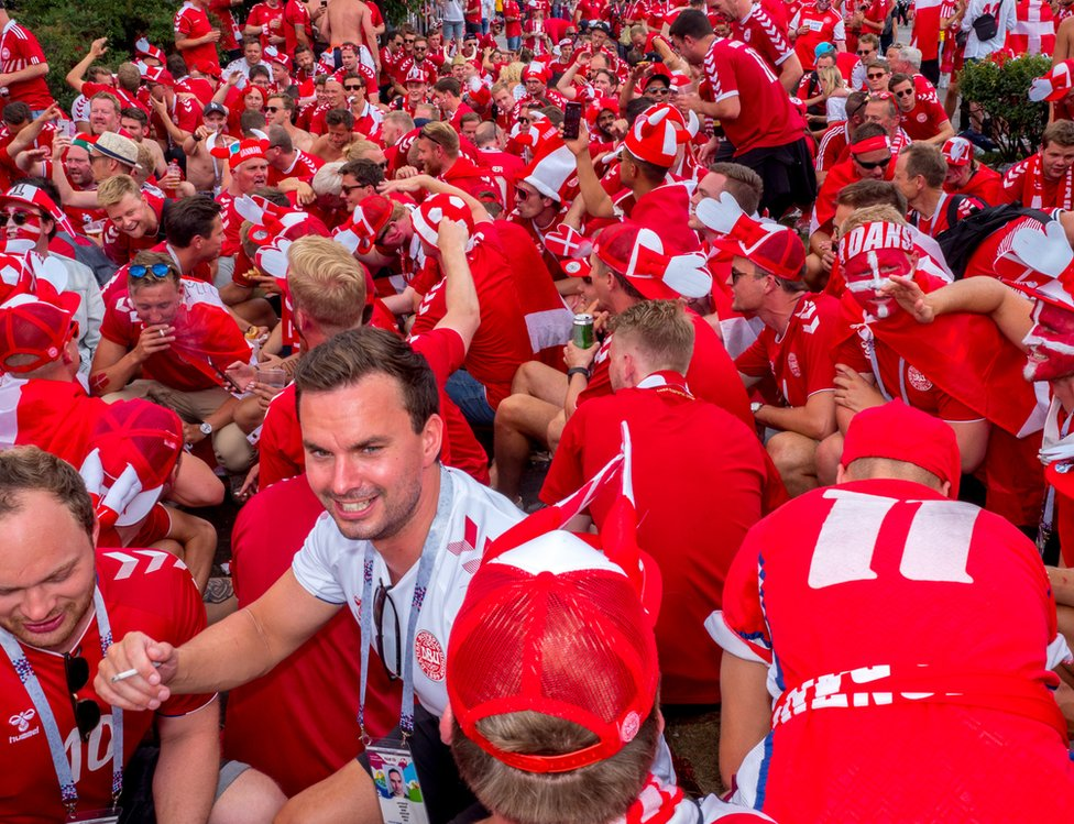 Danish fans drink beer and sing in central Moscow