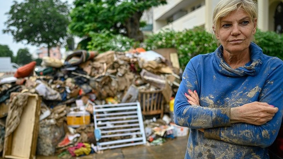 A resident in the Rhineland-Palatinate district of Ahrweiler stands in front of her property destroyed by a flood on 16 July 2021