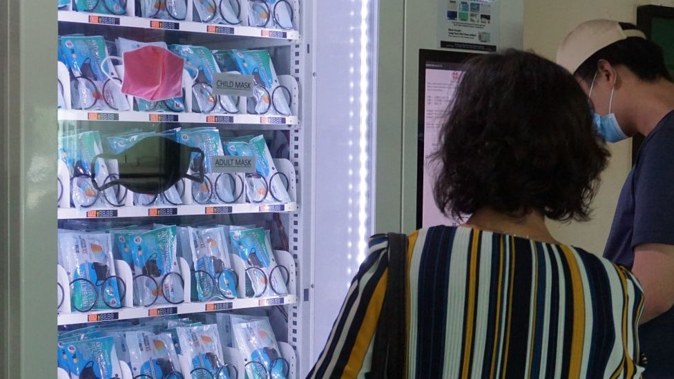 Man and woman in Singapore looking at face masks in a vending machine