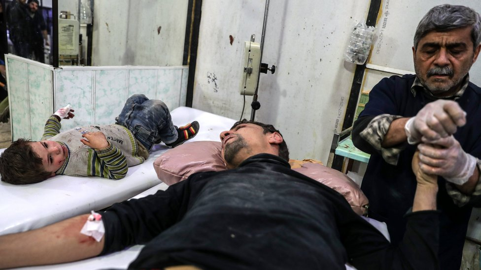 A man and a child injured by government bombardment in rebel-held Douma, Syria, receive medical attention at a field hospital (27 November 2017)