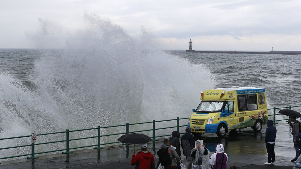 Wave next to ice cream van at seafront