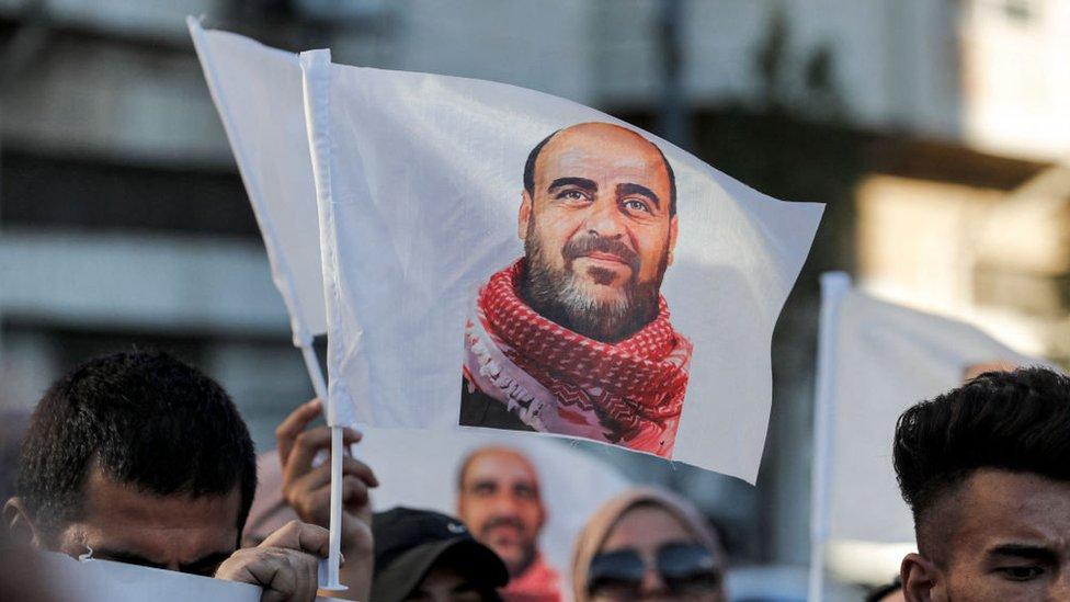 متظاهرون يرفعون صور الناشط الفلسطيني الراحل نزار بنات، أثناء مسيرة في مدينة الخليل بالضفة الغربية، 13 يوليو/تموز 2021