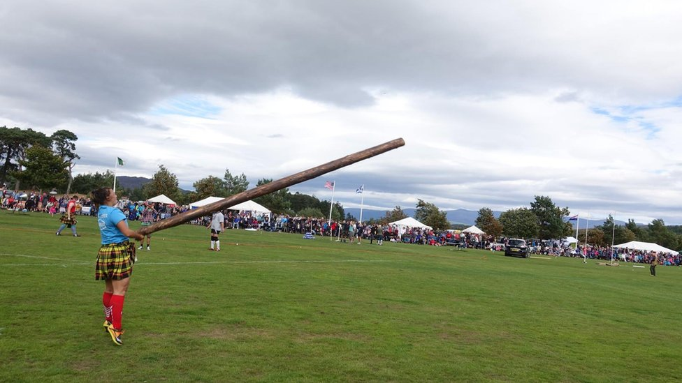 Celine Freeman-Gibb throwing a caber at a games in Scotland