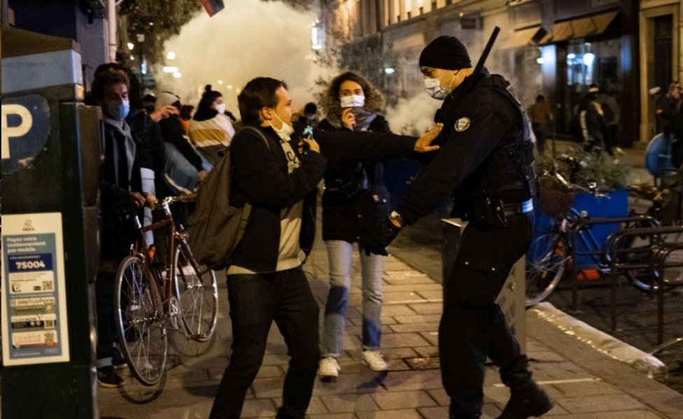 Protester and policeman in street in Paris, with tear gas cloud, 23 Nov 20