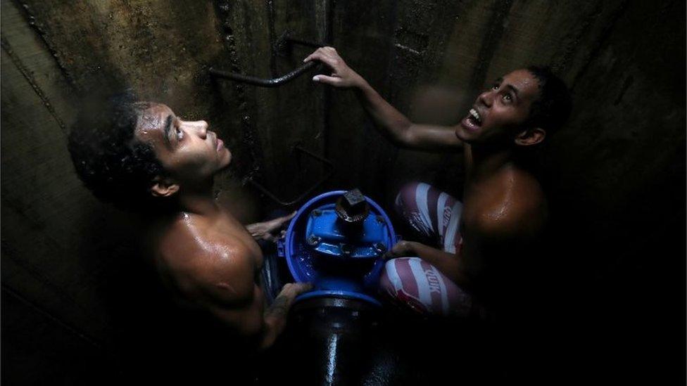 Locals collect water from an underground water main pipeline in Caracas, Venezuela March 12, 2019.