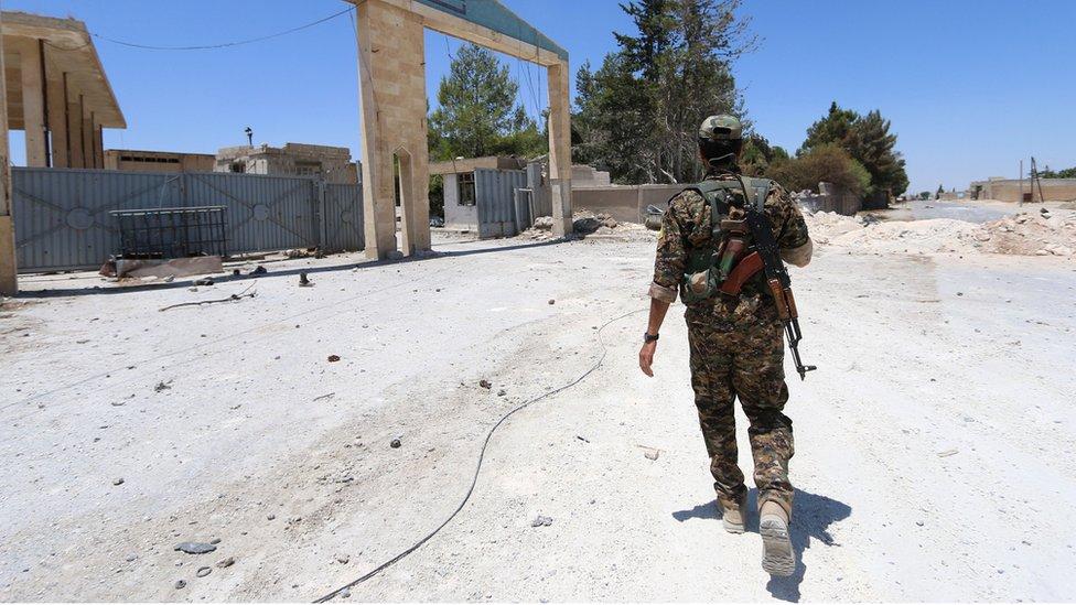 A soldier in camouflage walking across sandy ground in Manbij, 1 July 2016