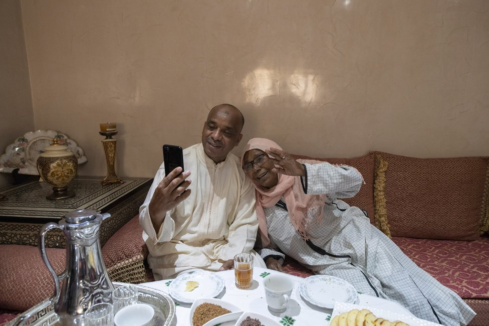 A Moroccan couple talk and waves to relatives on a smartphone as they celebrate Eid al-Fitr at home.