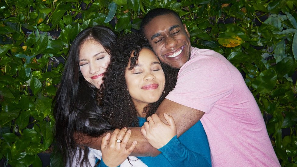 A man and two women embrace