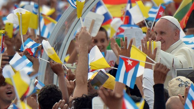 Pope almost obscured by a mass of flags and waving hands as he greeted by crowds in Havana
