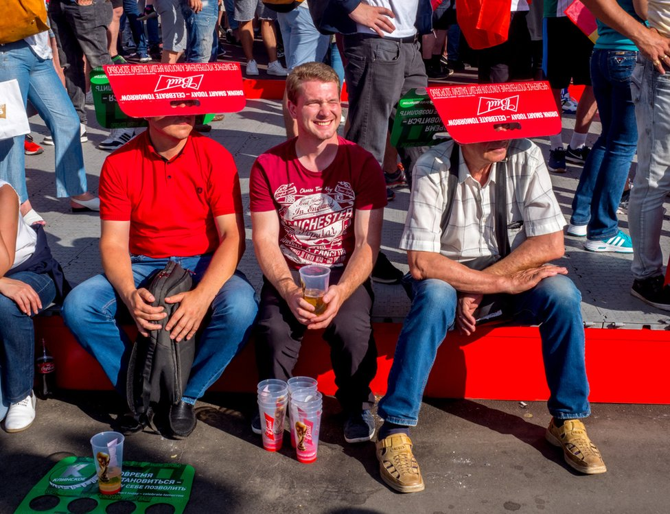Football fans with makeshift sunshades