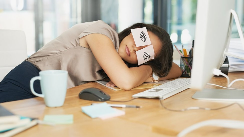 woman asleep at work, with head resting on her desk and post it notes on her eyes pretending to be awake