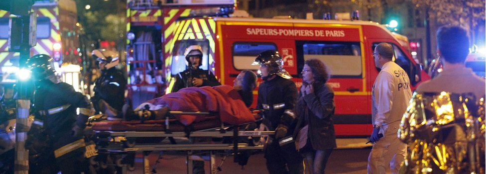Medics move a wounded man near the Boulevard des Filles-du-Calvaire after an attack 13 November 2015 in Paris, France