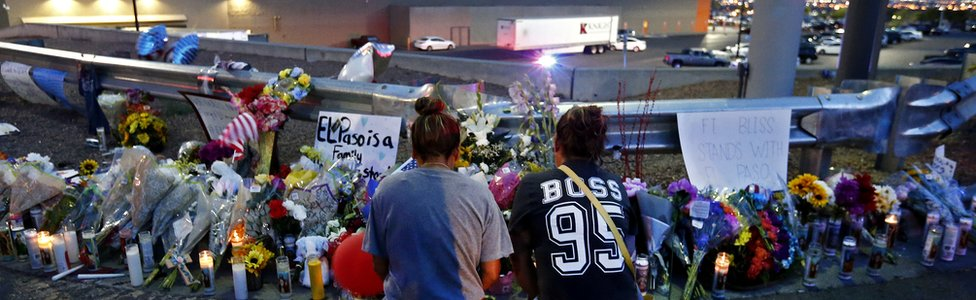 Two women kneel to pray at a memorial at the site of a mass shooting at a Walmart in El Paso, Texas