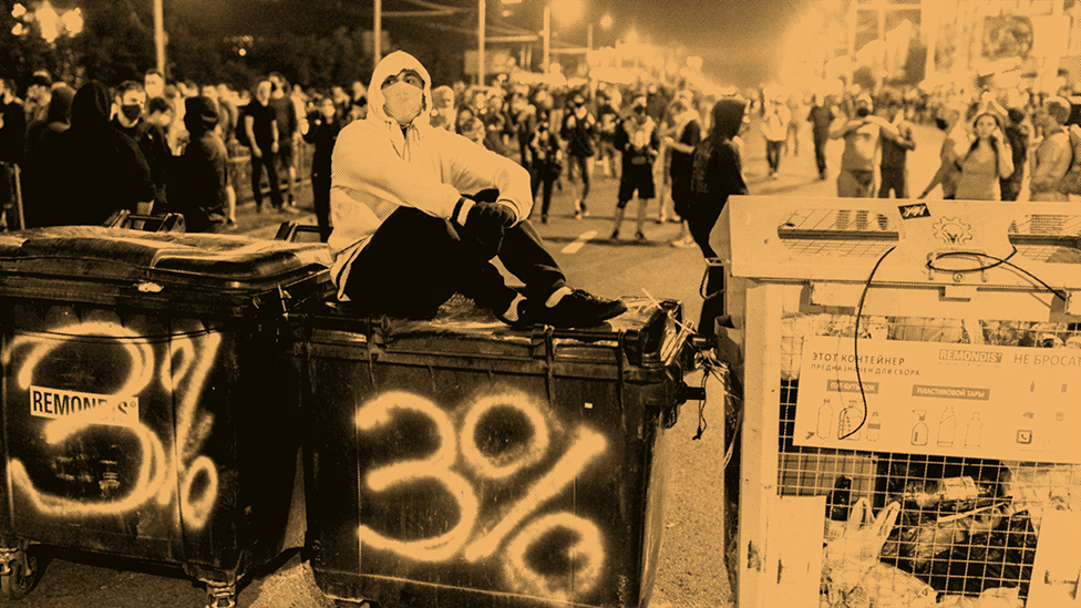 A protester sits atop a large rubbish container with a graffiti that reads '3%'.
