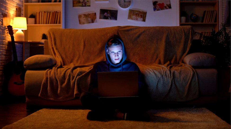 Adolescente lee de una laptop.