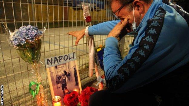 A Napoli fan cries while looking at Maradona tributes