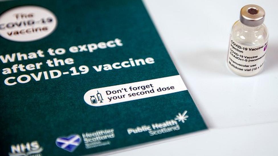 """Caderneta com dizeres em inglês """"O que esperar após a vacina contra a covid-19"""" e uma ampola de vacina"""