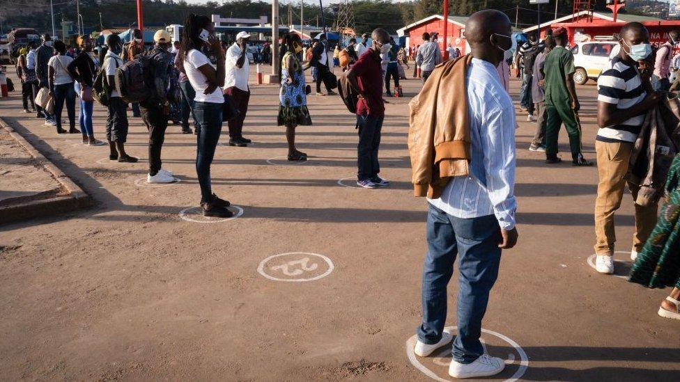 Personas haciendo cola mientras esperan montarse en un autobús en Ruanda.