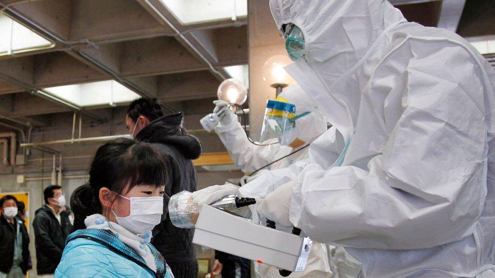 Un funcionario cubierto en un traje de protección nuclear mide los niveles de radiación en una niña