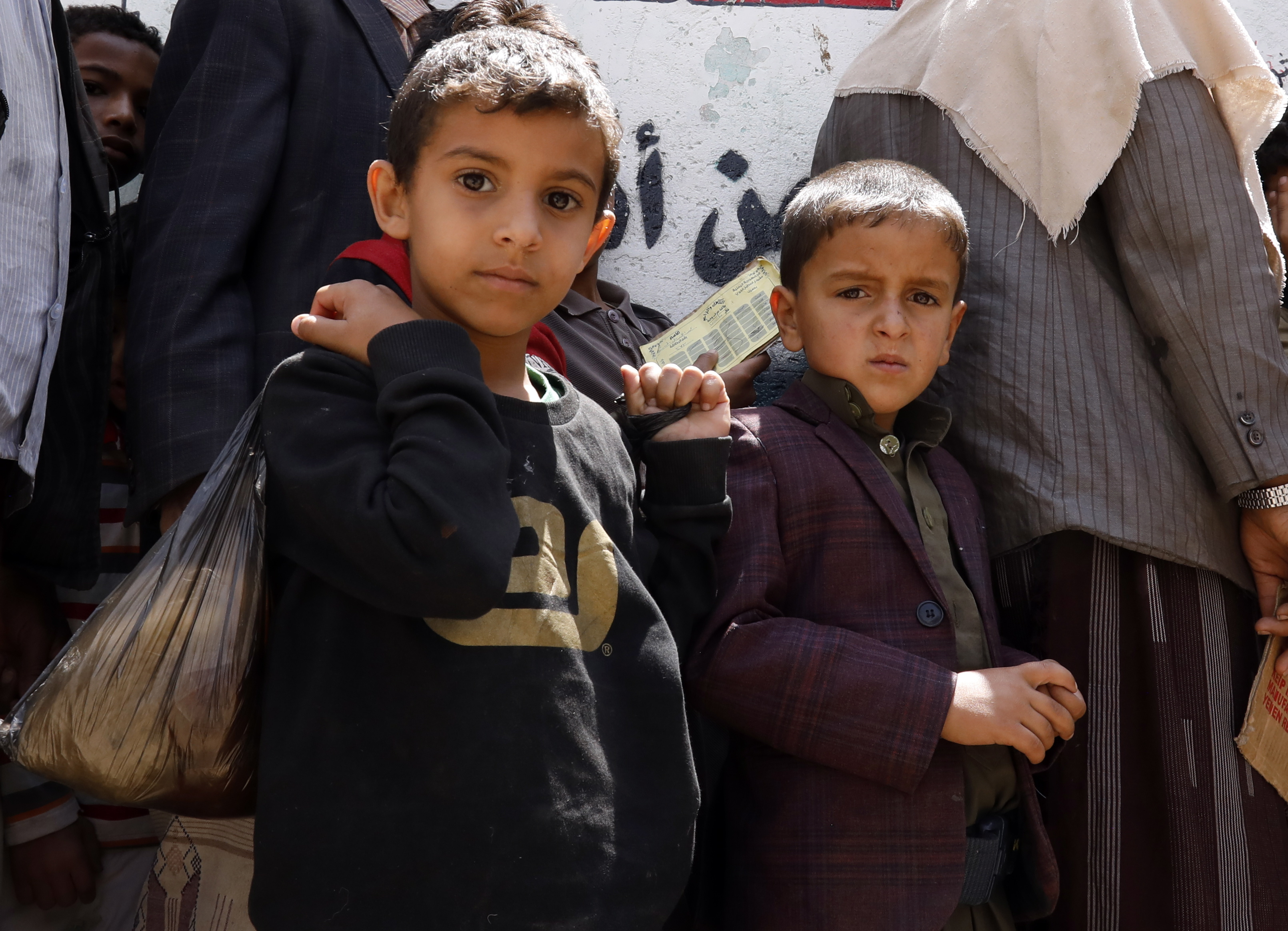 Yemeni children wait to get free food rations from a charity group in Sanaa, April 2020