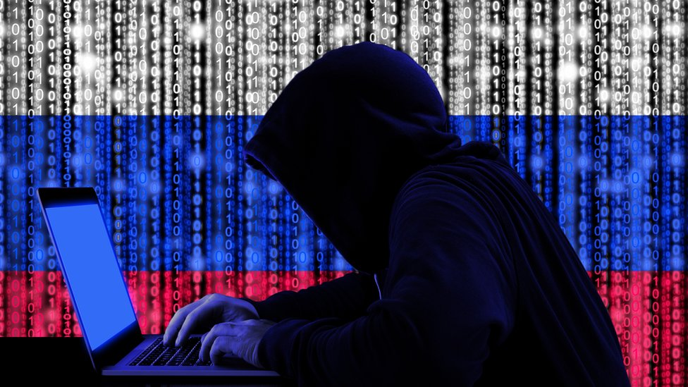 Encapuchado con computadora frente a una bandera rusa